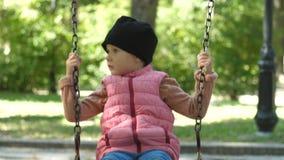Милая девушка около 4 лет старого едет на качании на красивый солнечный день осени в парке День семьи акции видеоматериалы