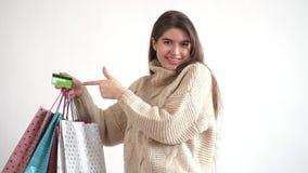 Милая девушка поднимает руку с пуком хозяйственных сумок и кредитной карточки И он указывает на карту акции видеоматериалы