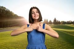 Милая девушка показывая большие пальцы руки вверх outdoors стоковые изображения rf