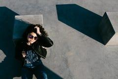 Милая девушка при вьющиеся волосы отдыхая в парке скейтборда Портрет красивой маленькой девочки в парке конька Маленькая девочка  Стоковая Фотография RF