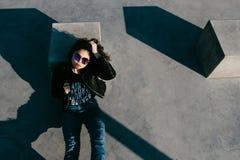 Милая девушка при вьющиеся волосы отдыхая в парке скейтборда Портрет красивой маленькой девочки в парке конька Маленькая девочка  Стоковые Фотографии RF
