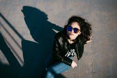 Милая девушка при вьющиеся волосы отдыхая в парке скейтборда Портрет красивой маленькой девочки в парке конька Маленькая девочка  Стоковая Фотография
