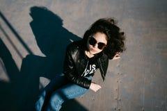 Милая девушка при вьющиеся волосы отдыхая в парке скейтборда Портрет красивой маленькой девочки в парке конька Маленькая девочка  Стоковое Фото
