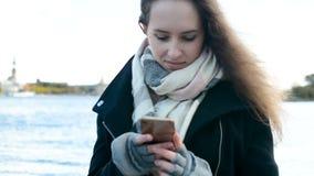 Милая девушка при красивые длинные волосы отправляя СМС, используя smartphone мобильного телефона outdoors видеоматериал