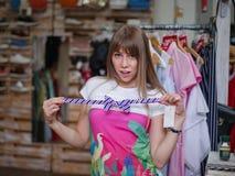 Милая девушка пробуя на бабочке на предпосылке магазина Красивая женщина в магазине одежды Ходить по магазинам аксессуаров Стоковые Изображения RF