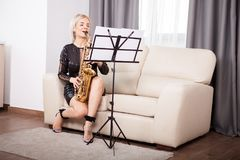Милая девушка саксофониста играя на ее музыкальном инструменте в Стоковое Фото