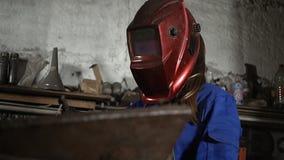 Милая девушка сварщика в форме в гараже работая с сварочным оборудованием Работа ` s женщин в искусстве акции видеоматериалы