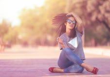 Милая девушка сидя на поле с двигая волосами стоковая фотография rf
