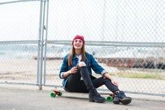 Милая девушка сидя на скейтборде outdoors на предпосылке природы Стоковые Изображения RF