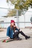 Милая девушка сидя на скейтборде outdoors на предпосылке природы Стоковое фото RF