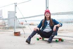 Милая девушка сидя на скейтборде outdoors на предпосылке природы Стоковая Фотография