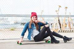 Милая девушка сидя на скейтборде outdoors на предпосылке природы Стоковые Фотографии RF