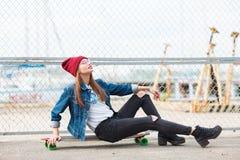 Милая девушка сидя на скейтборде outdoors на предпосылке природы Стоковое Изображение