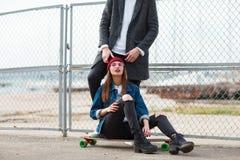 Милая девушка сидя на скейтборде outdoors на предпосылке природы Стоковые Изображения
