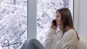 Милая девушка сидя на windowsill говоря на smartphone внешняя зима видеоматериал