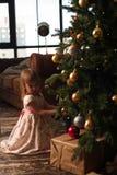 Милая девушка сидя около рождественской елки с подарками Стоковые Изображения