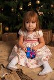 Милая девушка сидя около рождественской елки с подарками Стоковая Фотография