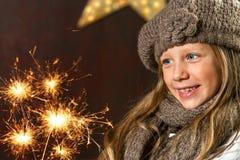 Милая девушка смотря праздничные искры пожара. Стоковая Фотография