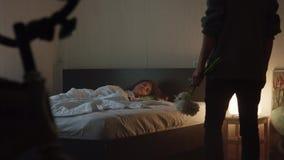 Милая девушка спит в спальне со светом на когда парень входит в комнату с цветками видеоматериал