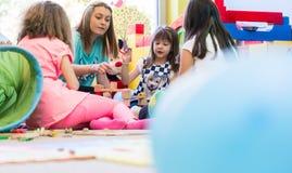 Милая девушка строя структуру от блоков игрушки во время playtime стоковые изображения rf