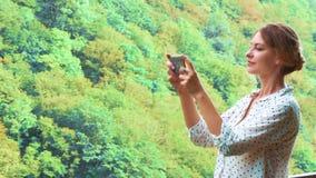 Милая девушка с белокурыми заплетенными волосами делает высококачественные фото на ее новом телефоне на мосте воздуха над скалой, акции видеоматериалы