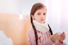 Милая девушка с большим серым цветом наблюдает держащ термометр Стоковые Фотографии RF