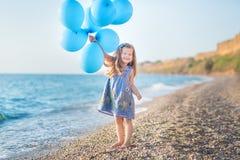 Милая девушка с воздушными шарами представляя на пляже морского побережья океана с песочной скалистой землей, праздником, отключе стоковая фотография