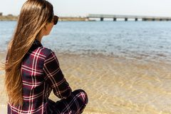 Милая девушка с длинными волосами идя на пляж моря стоковые фото