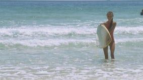 Милая девушка с доской серфинга идет вне от волн видеоматериал