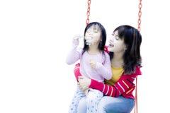 Милая девушка с ее матерью на качании Стоковое фото RF