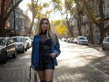 Милая девушка с пропуская волосами в куртке джинсовой ткани стоя на улице с припаркованными автомобилями стоковые фото