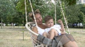 Милая девушка с ребенком отбрасывая на качании которое висит на дереве в парке Мальчик сидит на подоле его матери, они видеоматериал