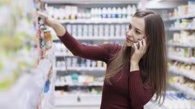 Милая девушка усмехаясь, говоря по телефону и ходя по магазинам в супермаркете сток-видео