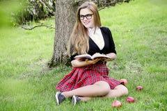 Милая девушка читая книгу, уча Стоковая Фотография RF