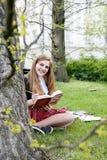 Милая девушка читая книгу, уча Стоковые Фотографии RF
