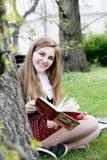 Милая девушка читая книгу, уча Стоковые Фото
