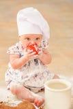 Милая девушка liitle в шляпе ` s шеф-повара сидя на почве пола кухни Стоковое Фото