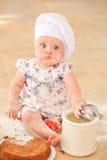 Милая девушка liitle в шляпе ` s шеф-повара сидя на почве пола кухни Стоковые Фото