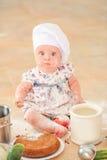 Милая девушка liitle в шляпе ` s шеф-повара сидя на почве пола кухни Стоковая Фотография