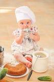 Милая девушка liitle в шляпе ` s шеф-повара сидя на почве пола кухни Стоковые Фотографии RF