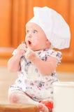 Милая девушка liitle в шляпе ` s шеф-повара сидя на почве пола кухни Стоковое Изображение