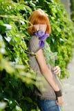 Милая девушка redhead с пурпуром подняла Стоковая Фотография