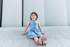 Милая девушка smilling около серой стены r стоковая фотография rf