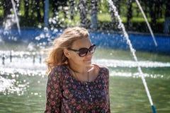 Милая европейская женщина в темных стеклах на предпосылке фонтана Стоковая Фотография