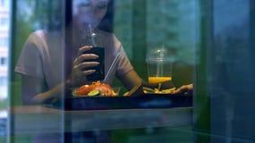 Милая женская выпивая carbonated вода от пластикового стекла, обедающего буфета стоковые изображения rf