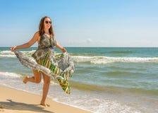 Милая женщина бежать вдоль пляжа Чёрного моря в одевать против неба стоковые изображения rf