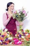 Милая женщина брюнета наслаждаясь ее букетом цветков стоковое фото