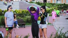 Милая женщина брюнета помогает ее женскому другу промелькнуть костюм плавания снаружи акции видеоматериалы