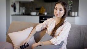 Милая женщина брюнет отдыхает на кресле в живущей комнате в телевизионных каналах праздника и переключения дистанционным управлен видеоматериал