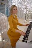 Милая женщина в желтом платье на рояле стоковая фотография